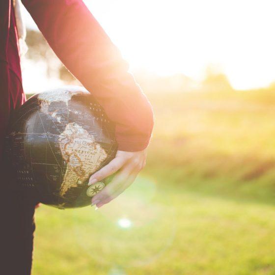 woman holding a globe by ben white