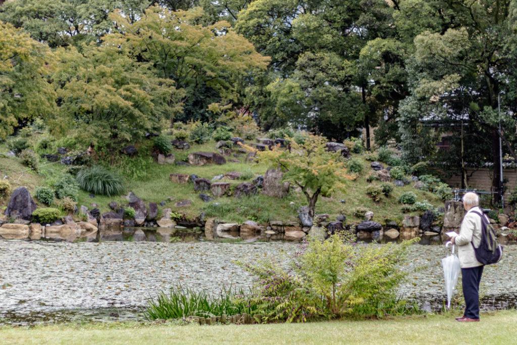 Un promeneur japonais observe le paysage au jardin Shosei-en de Kyoto