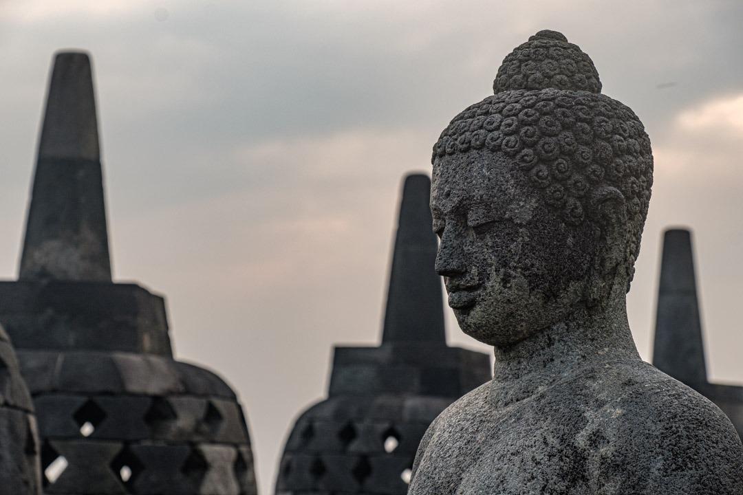 Un des nombreux bouddhas situés au sommet du temple de Borobudur