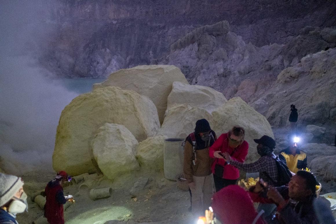 Les touristes équipés de masques à gaz devant des bloc de soufre - Kawah Ijen