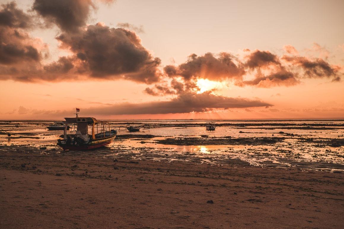 On assiste à un magnifique coucher de soleil sur la plage pendant la marée basse à Nusa Lembongan